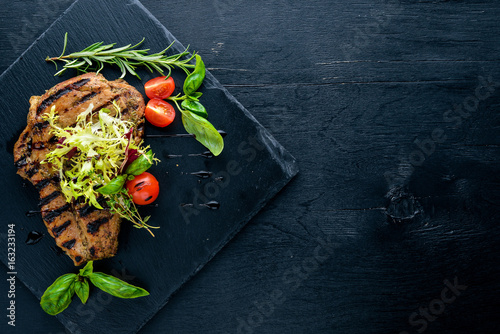 Veal steak cooked on grill. On a wooden background. Top review. Free space.