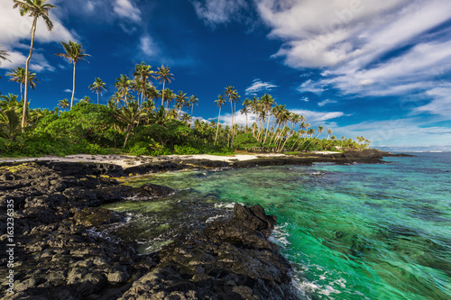 Beach with coral reef and black volcanic rocks on south side of Upolu, Samoa