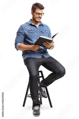 Guy sitting on a chair and reading a book