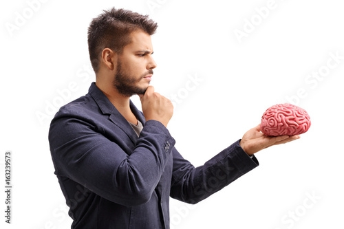 Pensive man looking at a brain model