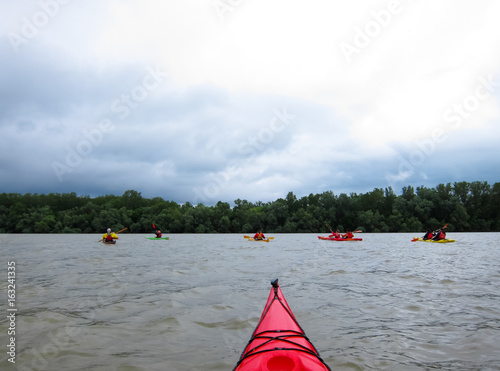 Nose of red kayak in Danube river on background of stormy cloudy sky