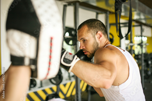 Boxer hitting the glove of his sparring partner. Men workout in gym.