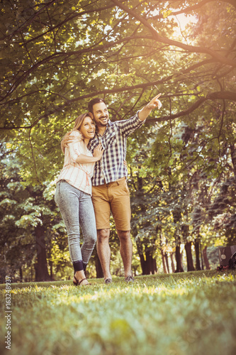 Young couple in hug walking on the meadow together. Boyfriend showing something to his girlfriend.