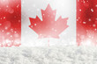 Defocused Canada flag as a winter Christmas background with falling snow, snowdrift and bokeh