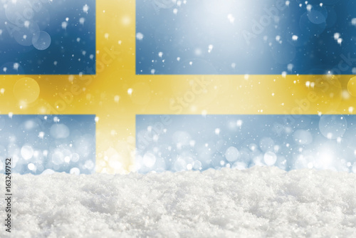 Papiers peints Stockholm Defocused Sweden flag as a winter Christmas background with falling snow, snowdrift and bokeh