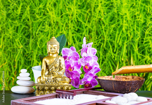 Buddha, orchid flower, rake, sand and zen stones as zen garden background