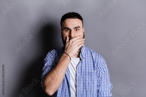 Surprised bearded man covering mouth with hand