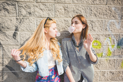 Plakát two beautiful blonde and brunette girl having fun in the city