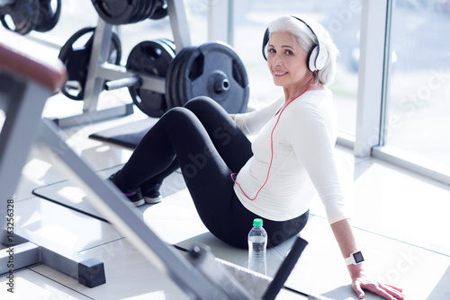 Elderly lady with headphones sitting at gym
