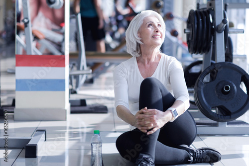 Smiling elderly lady sitting on floor at gym. - 163256370