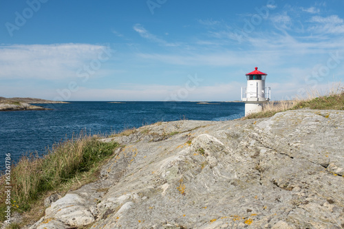 The beautiful little white lighthouse with its red ceilings, lit to control ships and boats, into the narrow passage from the sea into the beautiful Swedish archipelago, with the horizon and the blue