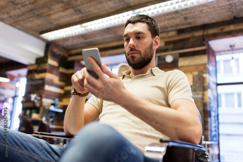 man with smartphone at barbershop or salon