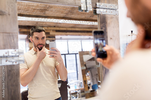 man taking selfie by smartphone at barbershop