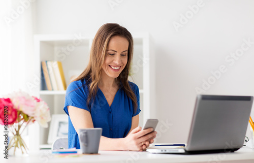 woman with smartphone and laptop at office