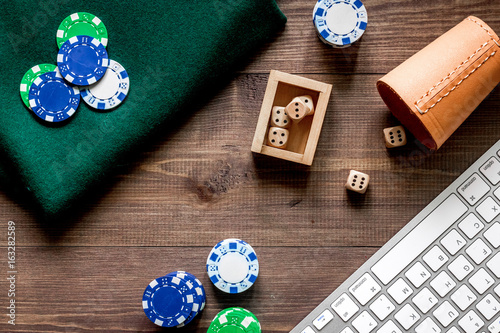 Poker chips and dices nearby keyboard on a wooden table top view плакат
