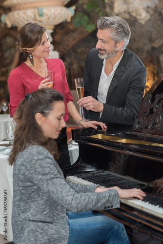 Couple enjoying glass of champagne while woman plays piano