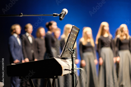 Microphone and music stand in front of electric pianos on the stage of the theater