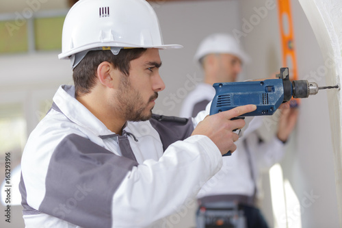 electric screwdriver in hand at a construction site Poster