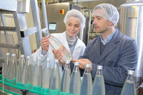 Man and woman examining bottle in factory