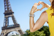 young woman showing heart shaped hands in Paris, France