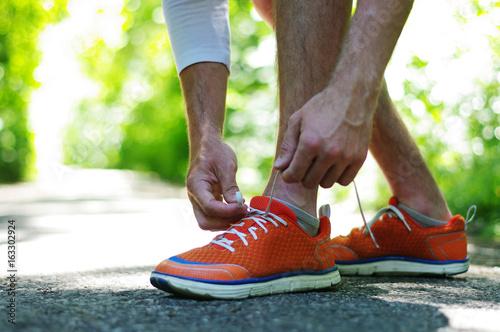 Aluminium Hardlopen Mann bindet seine Lauf-Schuhe um Joggen zu gehen