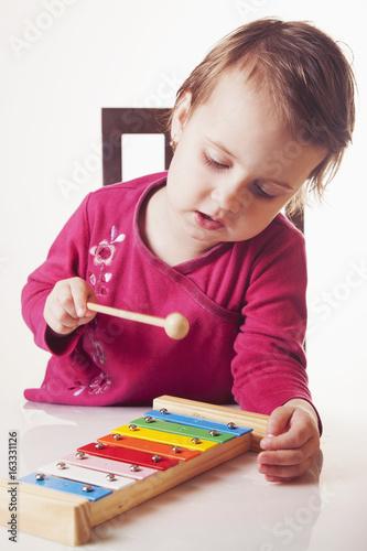 Plakát Beautiful child girl in music class