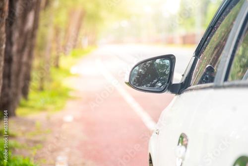 side rear-view car mirror parking on the roadside.