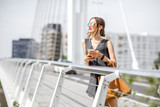 Portrait of a young businesswoman standing with phone and bag on the modern bridge in Nantes city in France - 163344175
