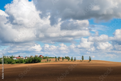 Beautiful autumn landscape with plowed field under blue sky with clouds