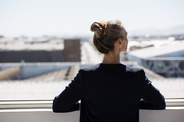 Rear view of thoughtful businesswoman looking through window