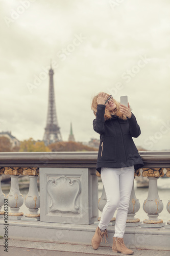 Cute female using cellphone with Paris background. Photo by astrosystem