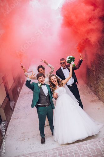 Newlyweds and their friends raise their hands with colors smoke. Running with smoke bombs. Red and blue colors. Wedding couple with color smoke.