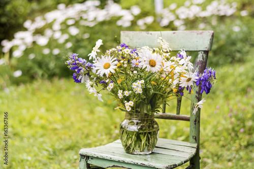 Foto op Plexiglas Landschappen vase with colorful flowers on a wooden chair