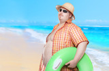 Obese man in shirt with green lifebuoy. Holidays on the beach. Funny lifeguard sending greeting from tropical paradise. - 163373792