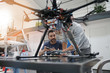 Engineer and technician working together on drone in office - 163392399
