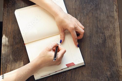 Kobieta zapisuje w kalendarzu notatkę Poster