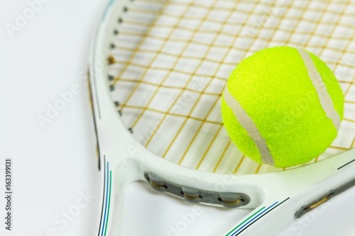 Tennis racket and ball on a white background