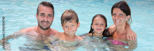 Young Family of four enjoying bathing in swimming-pool