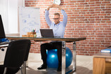 Happy Businessman Relaxing On Fitness Ball In Office - 163416516