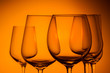 Set of wine glasses on orange background close up