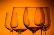 Set of wine glasses on orange background close up