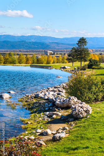 Beautiful autumn landscape view of the lake, pine trees, wooden chalets and mountains background