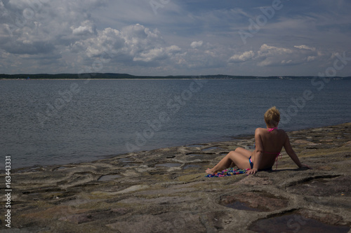 a lady sunbathes by the sea