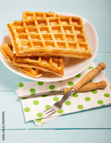 Freshly baked belgium waffles in plate. Breakfast concept with copy space on wooden background