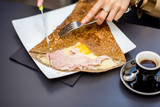Traditional french pancake called galette cooked with buckweat and stuffed with cheese egg and ham on the restaurant table with coffee - 163476315