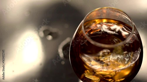 Ice cube throwing into brandy glass. Close-up view. Slow motion