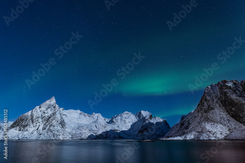 Steep winter mountains under Aurora Borealis lights in northern Norway