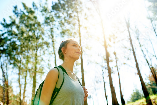 Smiling young woman hiking in a forest in summer - 163487134