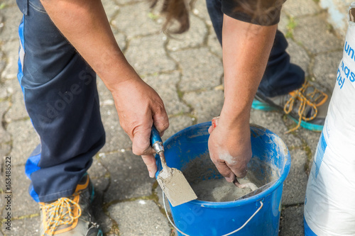 Two hands with bricklayer trowel, do prepare mortar. Poster
