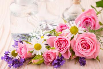 Spa still life - Ätherisches Öl in Glasflasche mit Rosen, Lavendel und Kamille